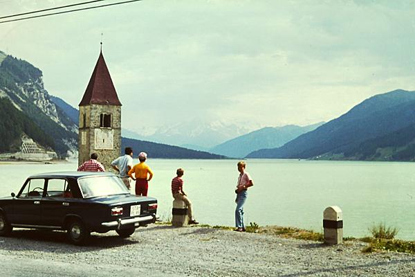 Touristen betrachten den Kirchturm von Altgraun am Reschenpass, der aus einem See herausragt.