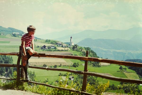Ein Junge hockt auf einem hölzernen Zaun am Ritten bei Bozen.