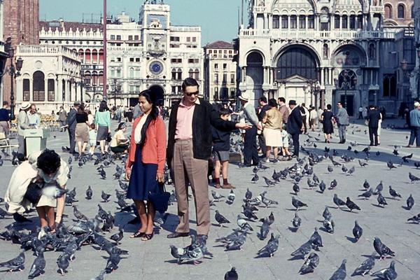 Paar und Menschen die Tauben füttern auf dem Markusplatz in Venedig.