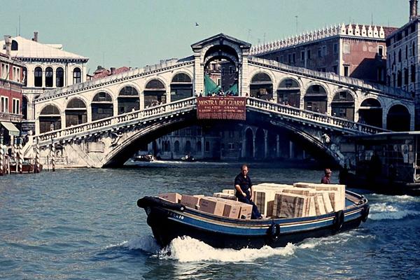 Schiff mit Kisten und im Hintergrund die Rialto Brücke mit Reklame (Mostra Dei Guardi) in Venedig.