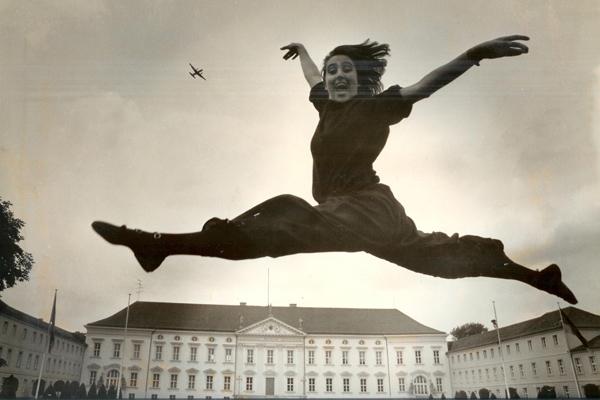 Eine Tänzerin springt über dem Schloss Bellevue mit einem Gesichtsausdruck der Leichtigkeit und Freude. Gleichzeitig fliegt ein Kleinflugzeug in Richtung rechten oberen Bildrand und kontraounktiert die Bewegung.