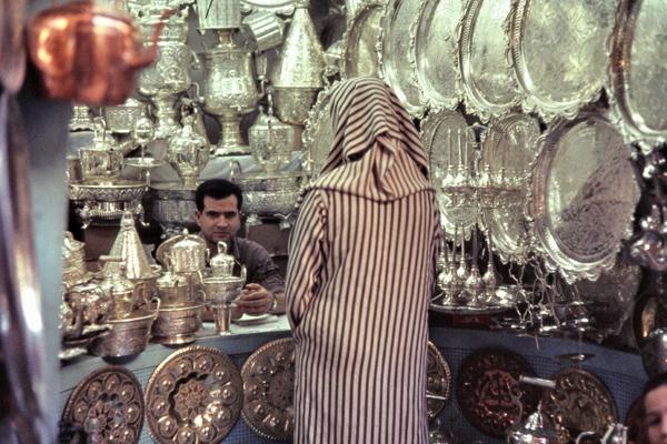 Ein Mann verkauft Silberschmiedarbeiten an eine Frau in einem Geschäft in den Souks in der Medina (Altstadt) von Fes.