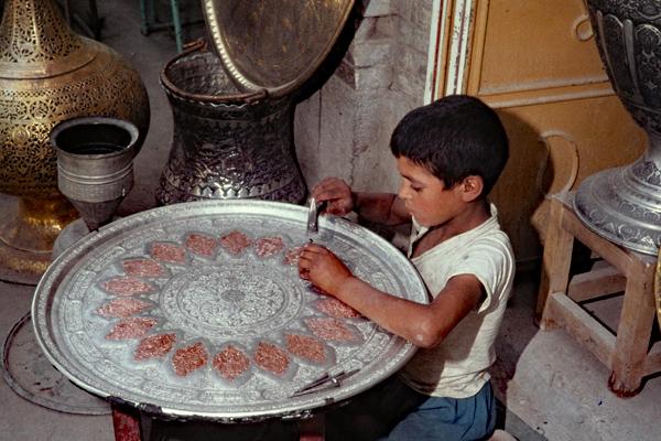 Junger Kupferschmied bei der Arbeit in einer Werkstatt am Meidan-i-Shah in Isfahan.