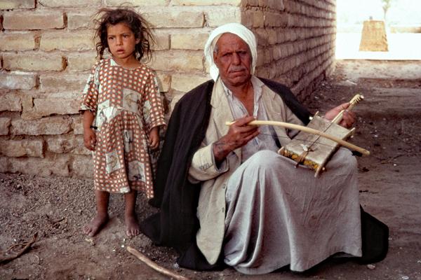 Ein Mädchen steht neben einem blinden Mann, der an einer Straßenecke auf einem Kamaneheh spielt.