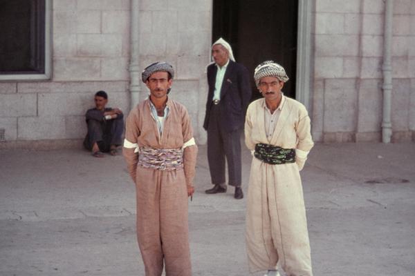Kurdische Männer in traditioneller Kleidung stehen am Bahnhof von Mosul.