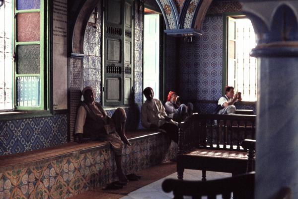 Männer sitzen in der mit bunten Fliesen ausgekleideten Synagoge Hara Sghira in Djerba.