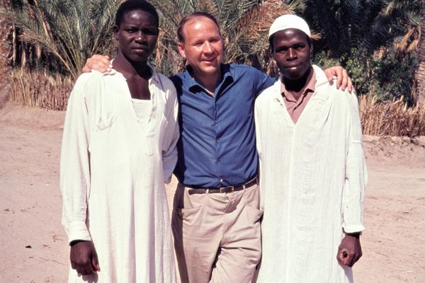 Ein europäischer Tourist posiert mit zwei afrikanischen Männern vor einer Oase in Tozeur.