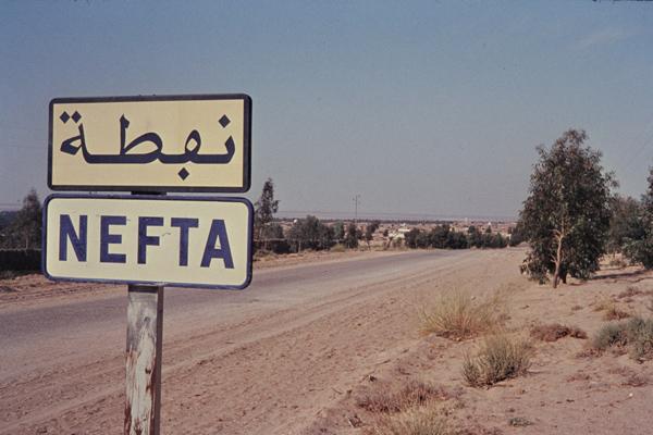 Das Ortsschild Neftas an der Straße vor der Stadt.