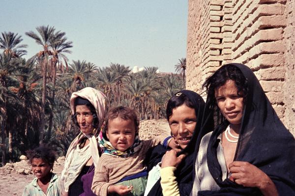 Frauen und Kinder sitzen vor einer Mauer gegenüber der Oase von Nefta.