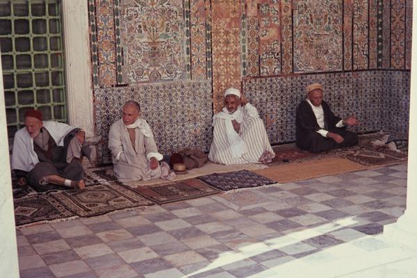 Muslimische Pilger sitzen auf Teppichen im Schatten vor der Barbiermoschee.