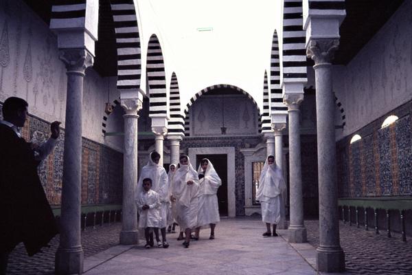 Frauen mit Kopftüchern und ein Kind zwischen den Säulen der Vorhalle der Barbiermoschee in Kairouan.