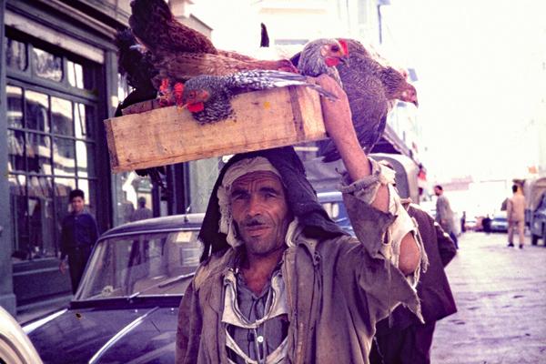 Ein Bauer mit einem Kasten voller Hühner auf dem Weg zum Markt.