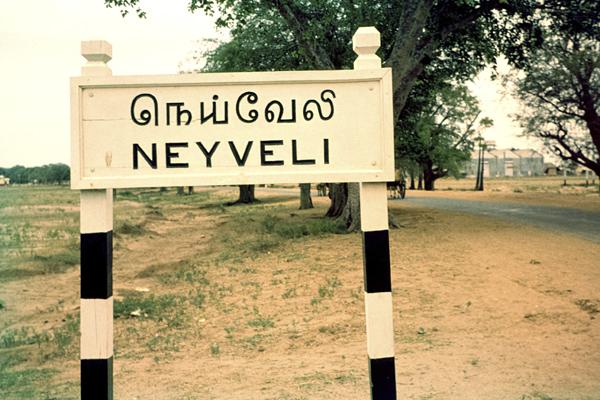 Ortstafel von Neyveli mit Straße und Häusern.