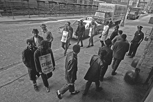 Ein Polizist beaufsichtigt streikende Männer mit Schildern in Manhattan in New York City.