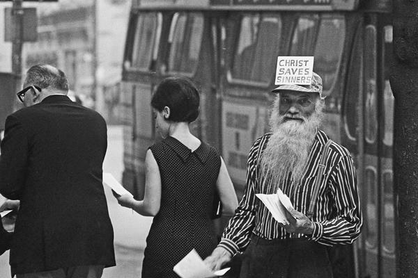 """Ein älterer Mann mit langem Bart und einer Mütze mit der Aufschrift """"Christ Saves Sinners"""" verteilt christliche Botschaften an Passanten an einer Straße in Manhattan in New York City."""