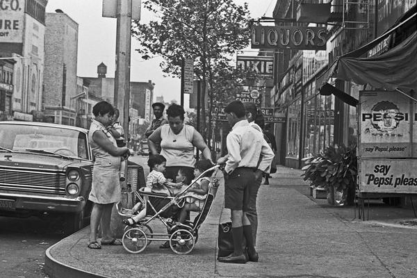Eine Familie mit drei Kindern in einem Kinderwagen an einer Straßenecke im New Yorker Stadtteil Harlem.