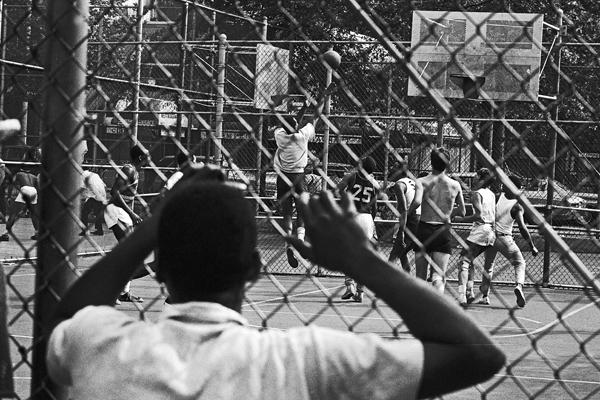 Ein Junge betrachtet ein Basketballspiel durch einen Gitterzaun in Manhattan in New York City.