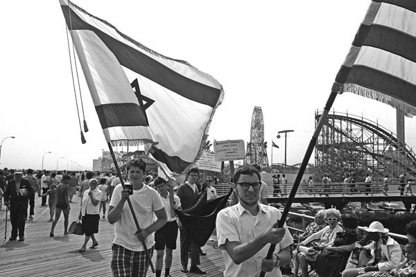 Pro-israelische Aktivisten schwenken israelische und amerikanische Fahnen während einer Demonstration auf einem Boardwalk auf Coney Island in New York.