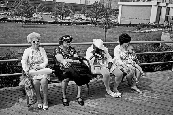 Vier Frauen mit Sonnenbrillen sitzen auf einer Parkbank in New York City.