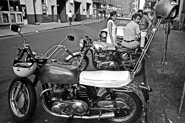 Eine Gruppe von Jugendlichen hockt neben ihren Motorrädern an einer Straße im New Yorker Stadtteil Greenwich Village.
