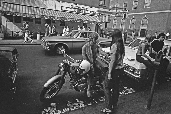 Jugendliche sitzen auf ihren Fahrzeugen an einer Straße gegenüber eines Restaurants im New Yorker Stadtteil Greenwich Village.