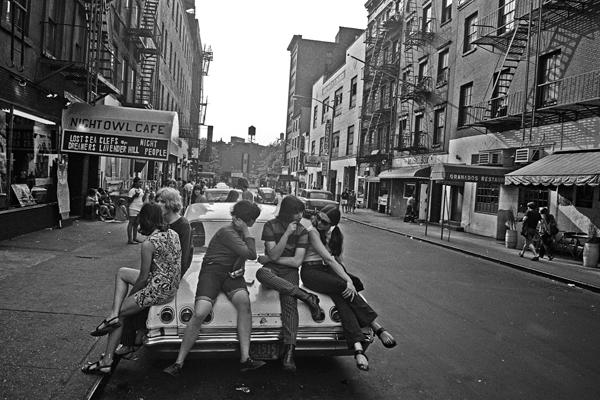 Eine Gruppe von Jugendlichen sitzt auf der Motorhaube eines Autos vor einem Café in einer Straße im New Yorker Stadtteil Greenwich Village.
