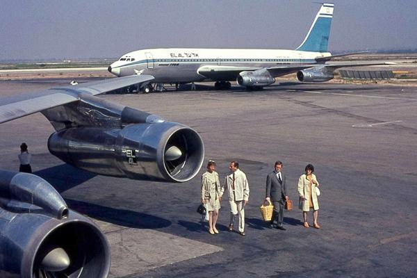 Passagiere auf dem Flughafen Ben Gurion in Lod. Neben ihnen und im Hintergrund sind Flugzeuge des Typs Boeing 707 der Israelischen Airline El Al zu sehen.