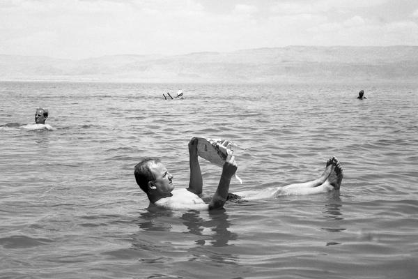 Ein Mann liegt auf dem Rücken im Wasser und liest eine Zeitung im Toten Meer , Israel 1968