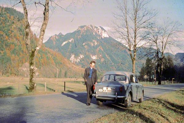 Ein junger Mann steht neben seinem Fiat Millecento auf der Staatsstraße 2060 zwischen Schloss Linderhof und Kloster Ettal.