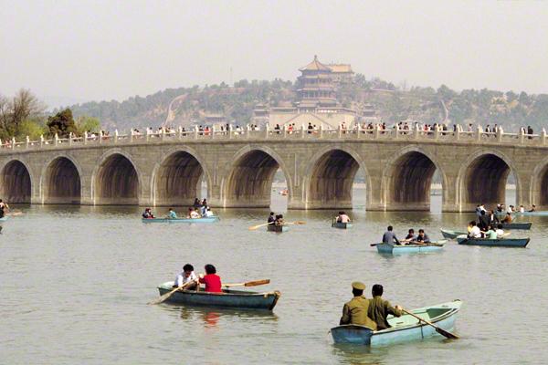 Ruderboote auf dem Kunming-See und die Siebzehn-Bogen-Brücke im Sommerpalast in Peking.