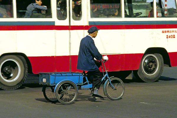 Ein alter Chinese auf einem Lastenfahrrad in der Innenstadt von Peking. Im Hintergrund ein Omnibus.