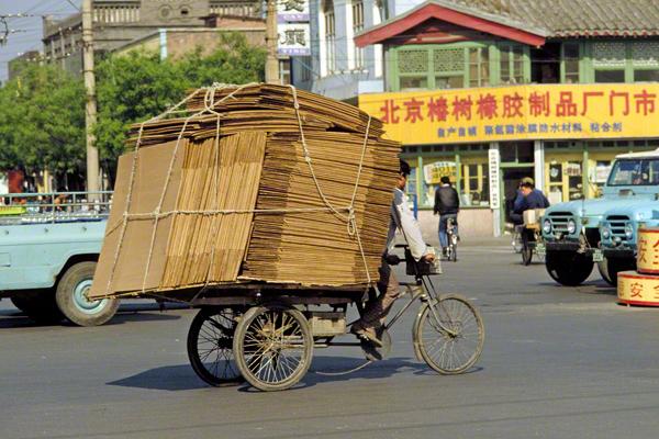 Mann mit schwerer Ladung auf seinem Fahrrad in der Innenstadt von Peking
