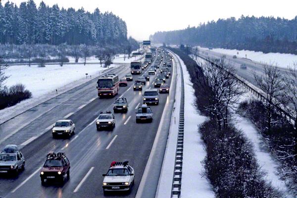 Dichter Reiseverkehr auf der verschneiten A99 Richtung Süden bei München.