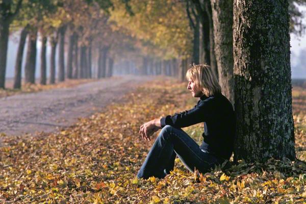 Ein junger Mann sitzt an einen Baum gelehnt in einer Ahorn Allee in Möschenfeld bei München.