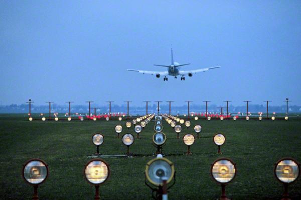 Landung eines Flugzeuges am Abend auf dem Flughafen München-Riem (Blick von Feldkirchen Richtung Westen). Im Vordergrund die Landebefeuerung.