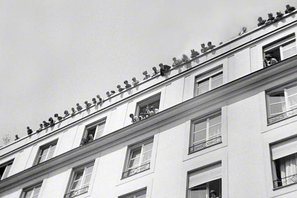 Mitglieder der Band The Beatles schauen aus dem Fenster des Hotels Bayerischer Hof in München. Auf dem Dach männliche und weibliche Fans.