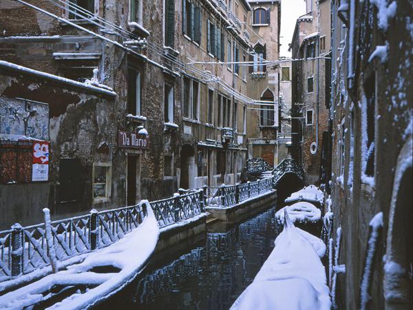 Eingeschneite Gondeln in Venedig, Italien.