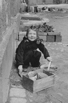 Ein Kind spielt mit Alltagsgegenständen, da es damals so gut wie keine Spielzeuge gab.
