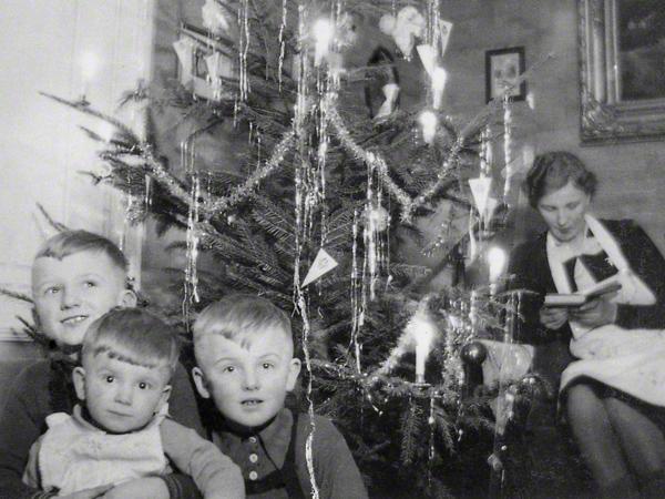 Mutter sitzt auf der Couch und liest in einem Buch. Vielleicht die Weihnachtsgeschichte? Drei Jungen sitzen unter einem Tannenbaum.