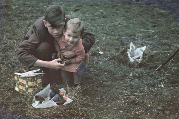 Zwei Kinder suchen Ostereier in Wildschönau in Tirol. Der Junge hält seine Schwester im Arm, vor ihnen steht ein Osternest.