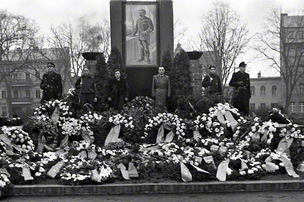 Uniformierte Männer stehen zwischen Grabkränzen an der Ehrenwache zu Stalins Tod im März 1953 in Fürstenwalde.