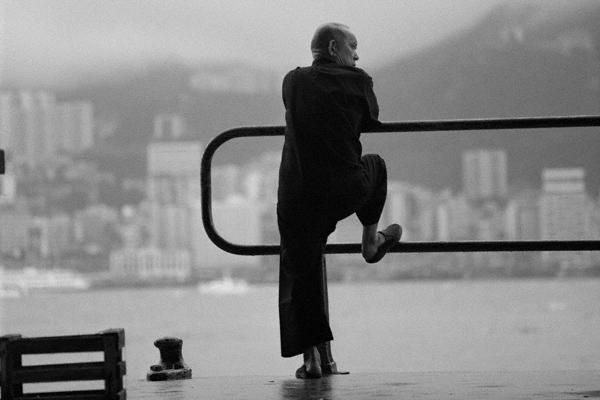 Ein Hafenarbeiter lehnt an einem Geländer am Hafen der Stadt Kowloon in Hongkong. Im Hintergrund sind Hochhäuser zu sehen.