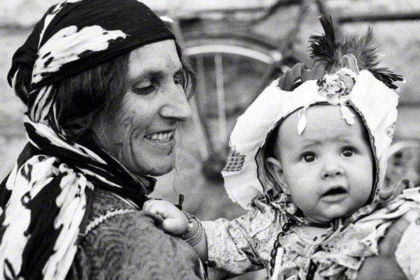 Eine Beduinenmutter sitzt am Straßenrand mit einem festlich herausgeputzem Kind.