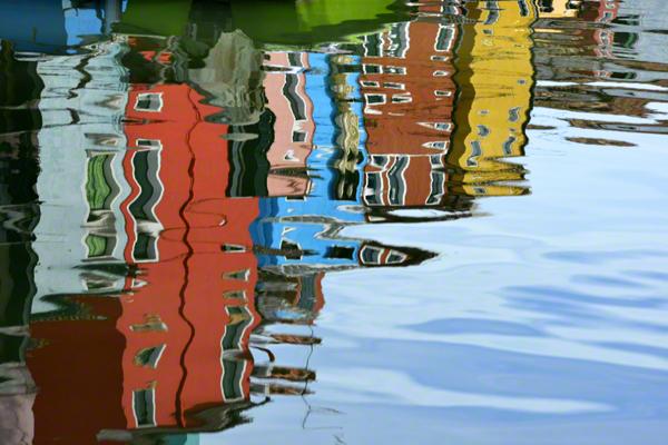Gebäude spiegeln sich im Wasser auf der Insel Burano bei Venedig.