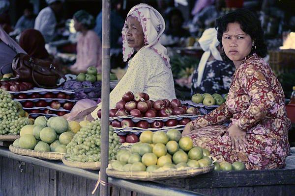 Zwei Frauen sitzen in Malaysia auf einem hölzernen Podest und verkaufen Obst in flachen Körben, darunter Äpfel, Trauben, Jackfrucht und Durianfrucht. Die Frau, die im Vordergrund sitzt, trägt ein rot geblümtes Kleid und goldene Ohrringe. Die ältere Frau im Hintergrund trägt ein weiß-rot gemustertes Kopftuch oder einen Turban und dazu ein weiß gepunktetes Kleid.