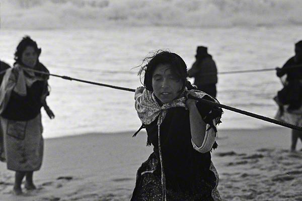 Frauen bringen Schleppnetze am Strand von Nazaré in Portugal ein.