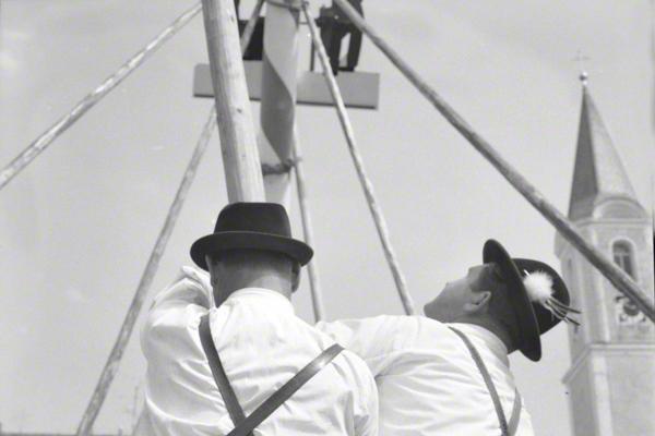 Männer in bayerischer Tracht stellen im oberbayerischen Glonn den Maibaum auf.