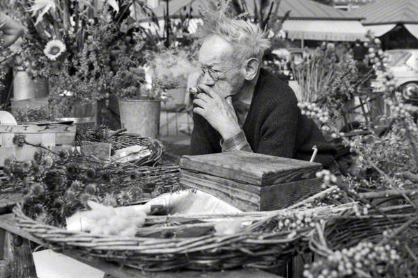 Blick auf einen Blumenstand auf dem Viktualienmarkt in München. Auf dem Stand liegen Blumen und Zweige von Bäumen. Dahinter der Händler. Er raucht Zigarre. Im Hintergrund weiter Stände.