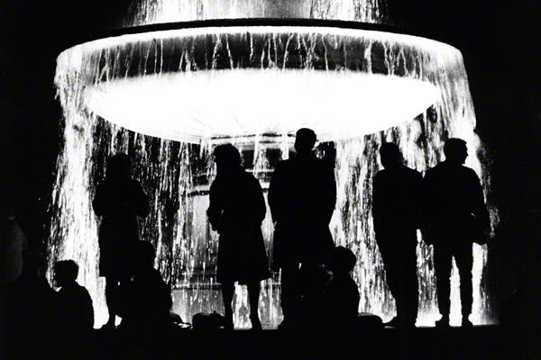 Bei Nacht beobachten Jugendliche von einem beleuchteten Brunnen an der Universität die Schwabinger Krawalle in München.