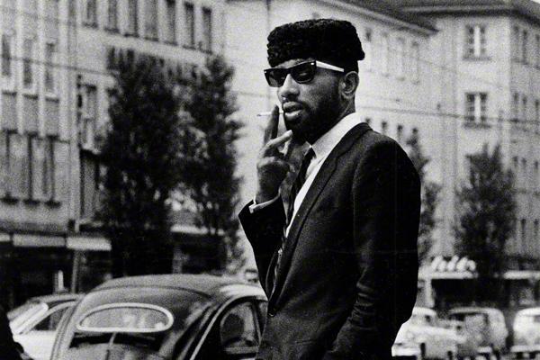 Ein Mann mit eleganter Kleidung, Hut und Sonnenbrille raucht eine Zigarette auf der Leopoldstraße in München.